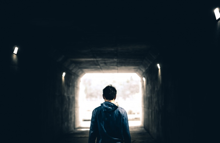 A man walking in a dark tunnel with light at the very end.