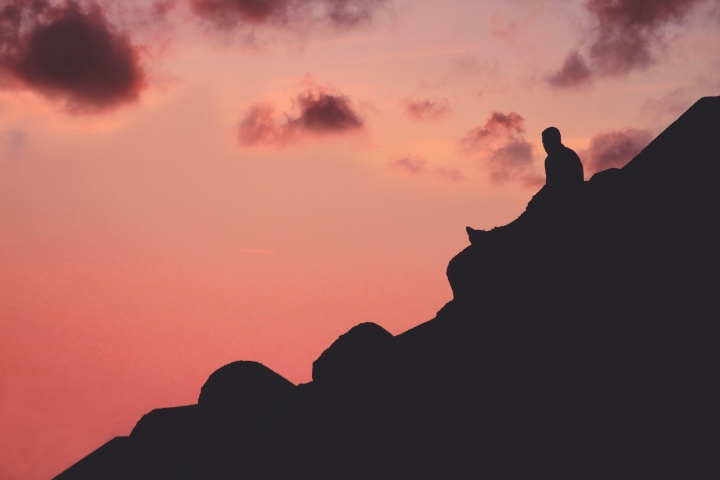 A person sitting a hill with a red sky.