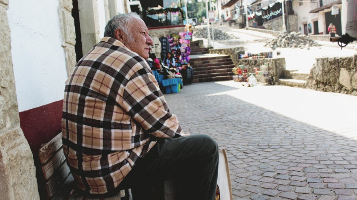 A old man sitting on a bench in an old village.