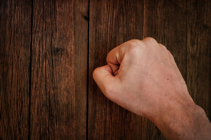 A close fist knocking on a door.