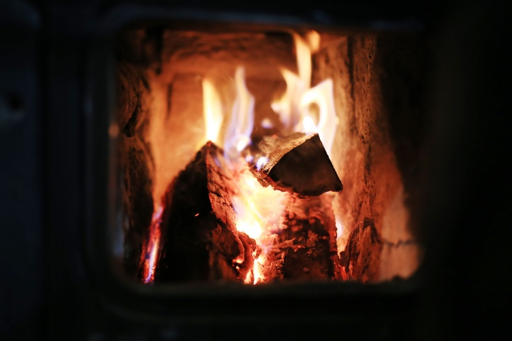 A fire burning inside a wood stove.