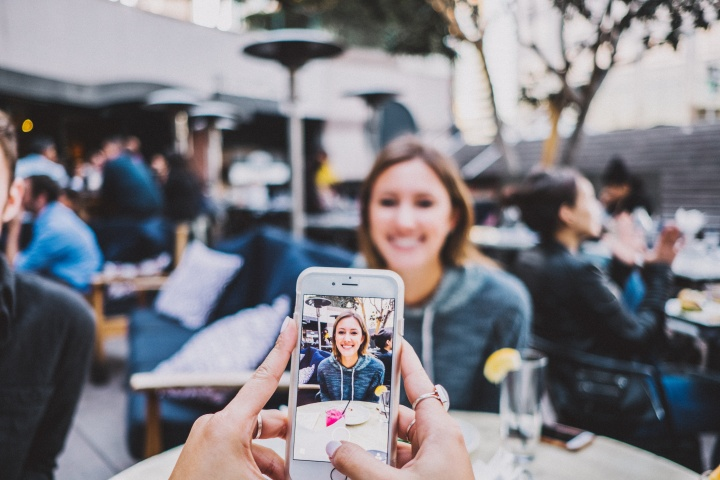 A woman taking a photo of another women with a smartphone.