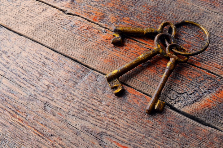 Three old skeleton keys laying on an old wood table.