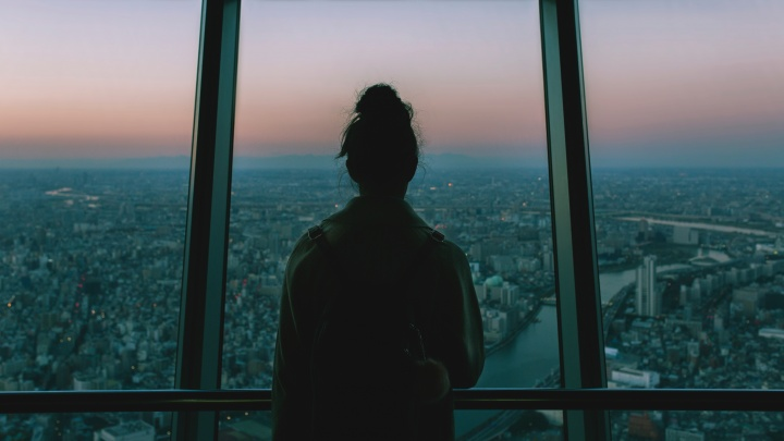 A woman looking outside of window of tall building.