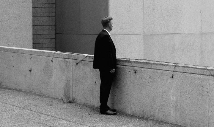 A man standing on walk way between buildings.