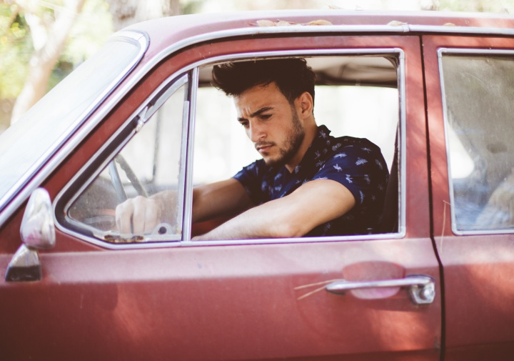 A young man sitting in the driver's seat of an old car.