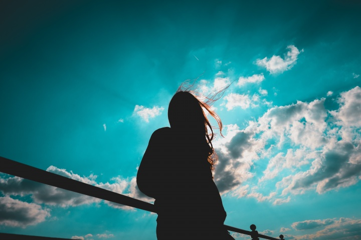 The silhouette of a young woman with the sky and sun in the background.