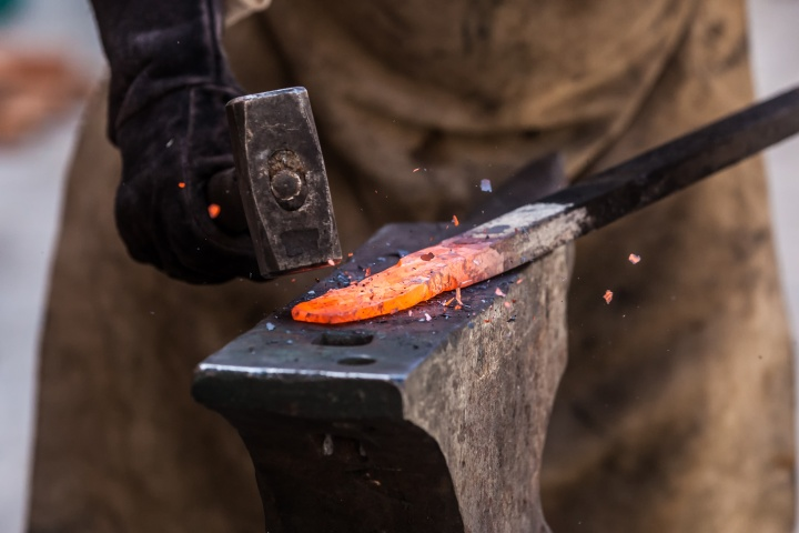 Close-up photo of a hammer striking a heated piece of metal.