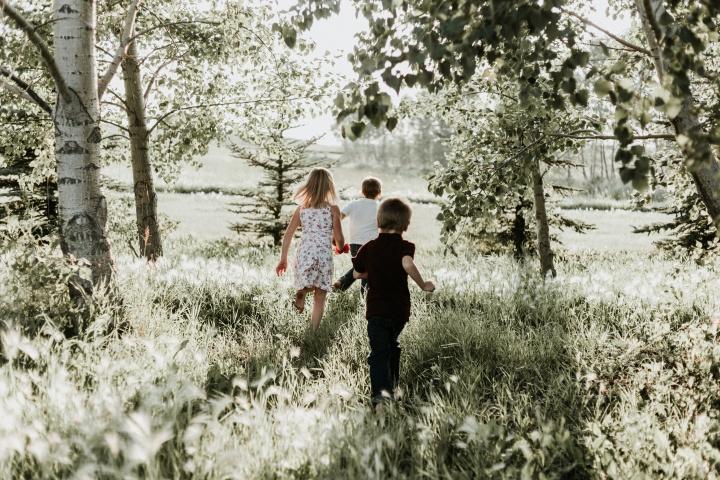 Three kids running through a field.