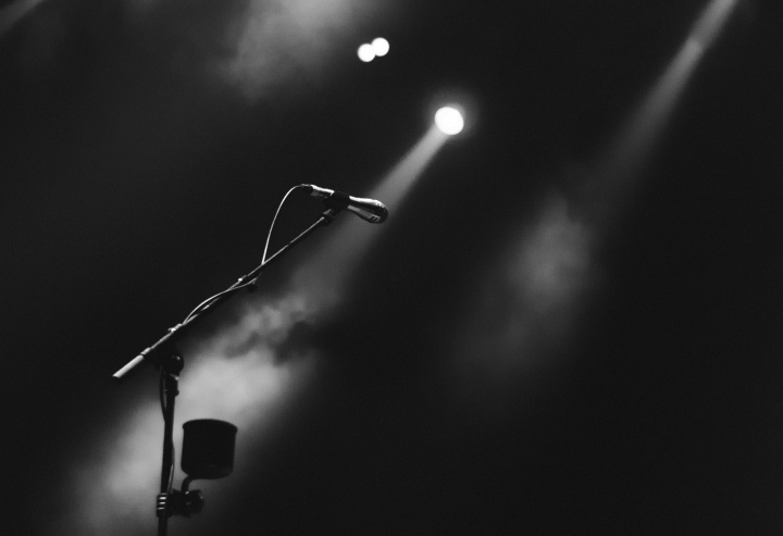 A microphone on a stage lit by a spotlight.