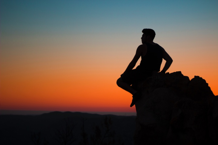 A man sitting on a rock with red sunset behind him.