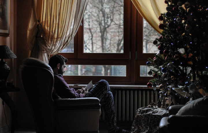 A man sitting in a chair across from a Christmas tree.