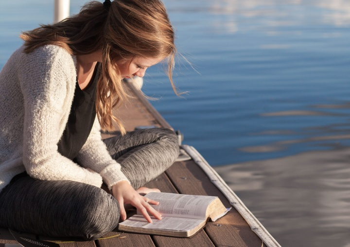 A woman sitting on a dock in the water reading her Bible.