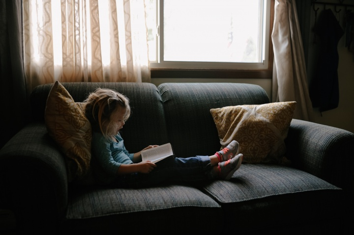 A little girl sitting on a couch looking at a Bible.