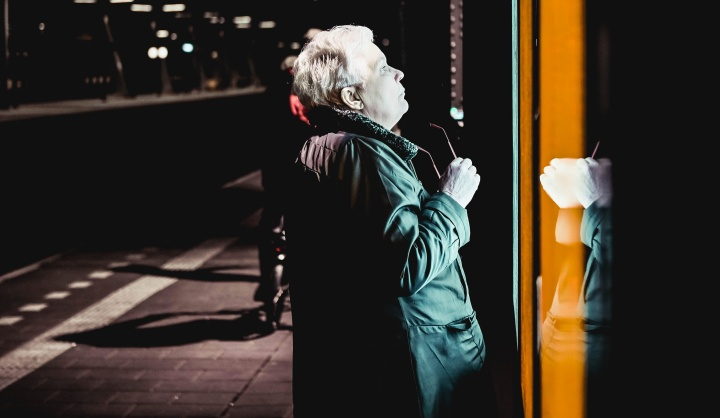 An older person looking into a store window at night.
