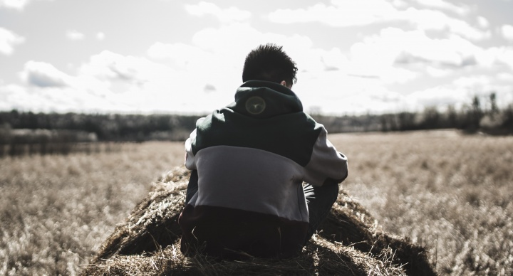 A young man sitting on a round bale of hale looking out over a field.