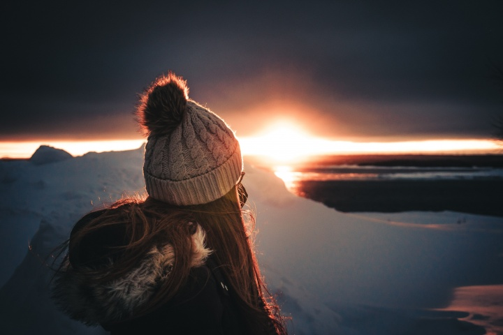 A woman who is warmly dressed watching the sunset.
