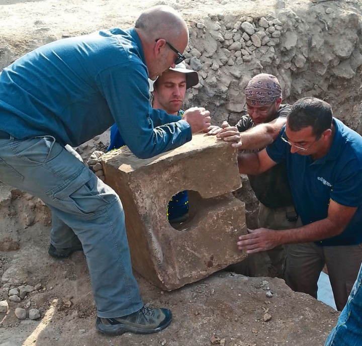 Diggers remove a stone toilet that was used to defile the shrine where the altar was found.