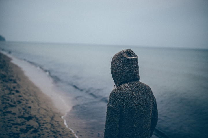 A person walking on a beach wearing a hoodie.