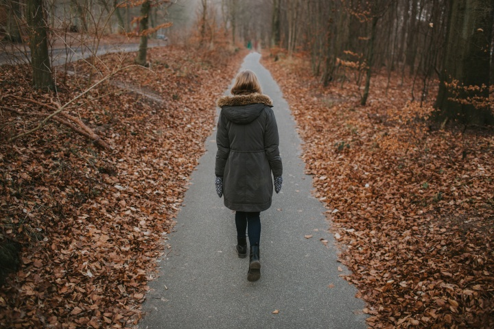 A woman walking on a paved path.