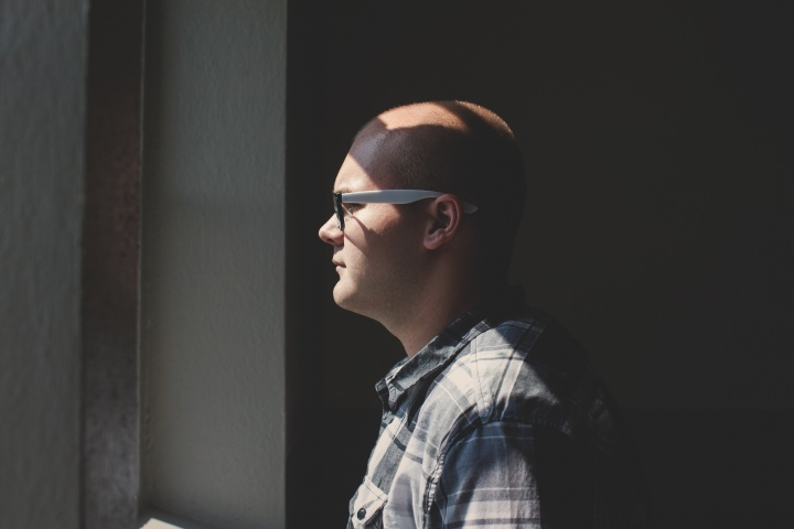 A man wearing glasses looking outside a window.