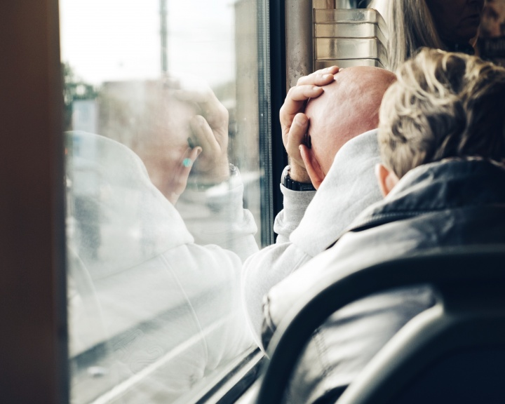 A man leaning his head against a train window.