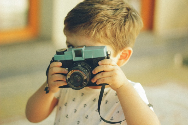 A little boy playing with a camera.
