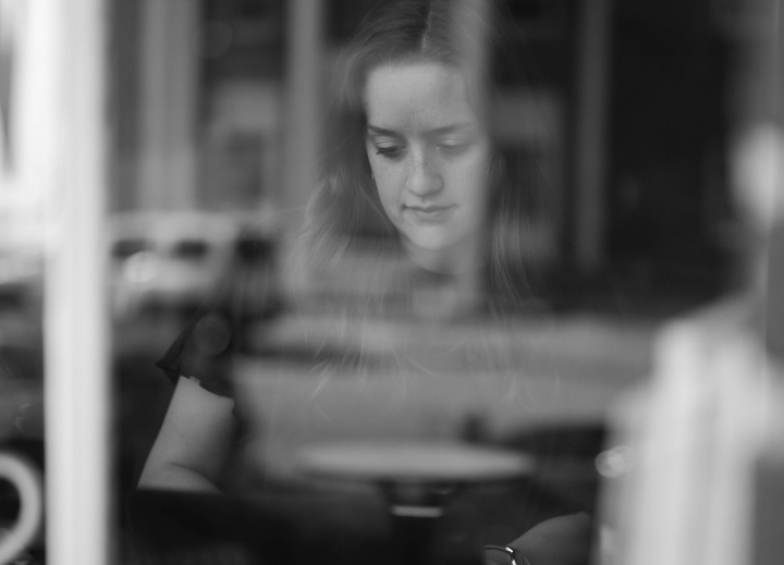 A young woman typing on a laptop at a counter of a cafe.