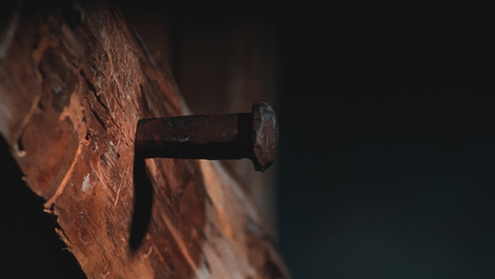 A old metal stake nailed into a wooden beam.