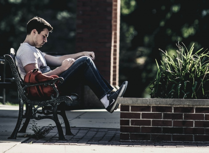 A man sitting on a park bench reading.