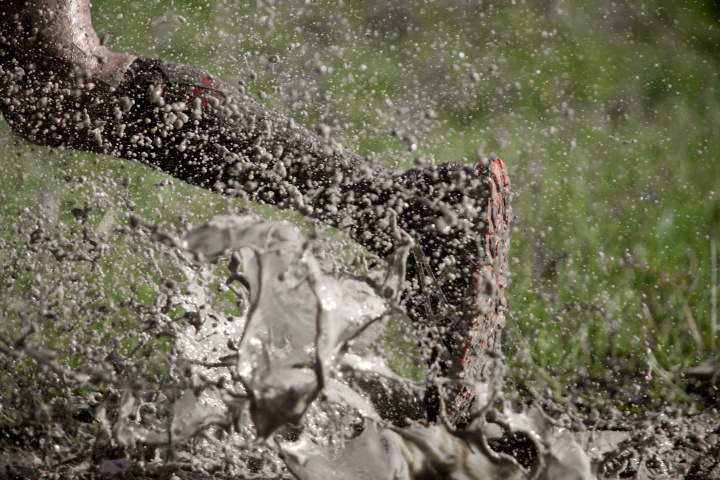 A person running through a mud puddle.
