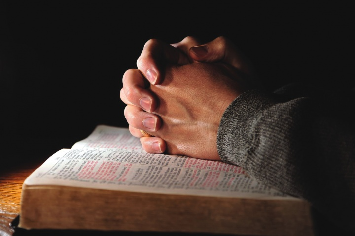 Clasped hands on top of an open Bible.