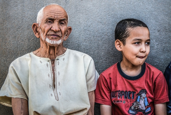 An old man (maybe the grandfather) and young boy sitting against a wall.