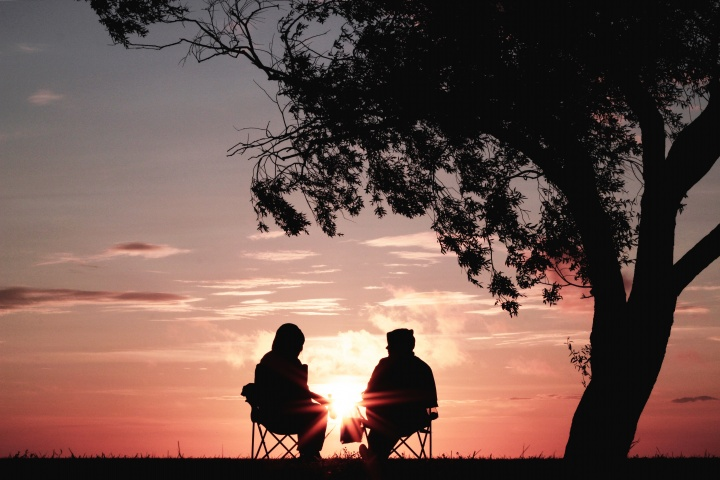 Two people sitting together talking as the sun is setting in the background.