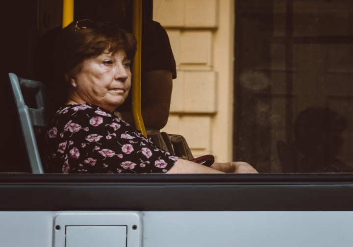 A women looking outside the window of a bus.