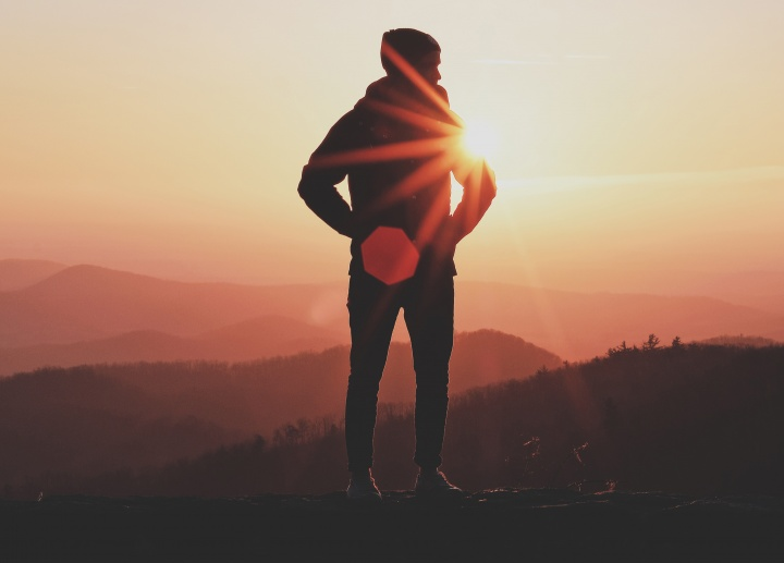 A person standing on the rock with the sun behind them.