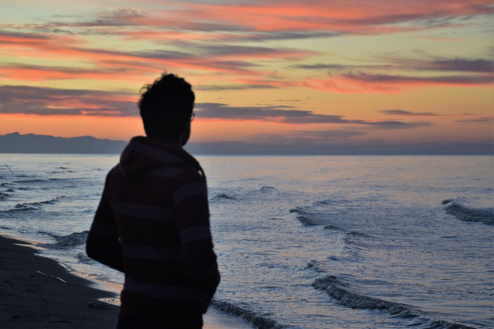 A man looking at a sunset over a body of water.