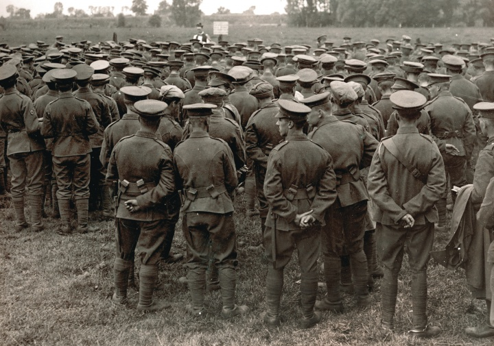 An old WWI photograph showing a church service in the field with soldiers watching a priest.
