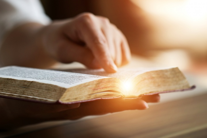 An open Bible with someone's hand pointing to a scripture.