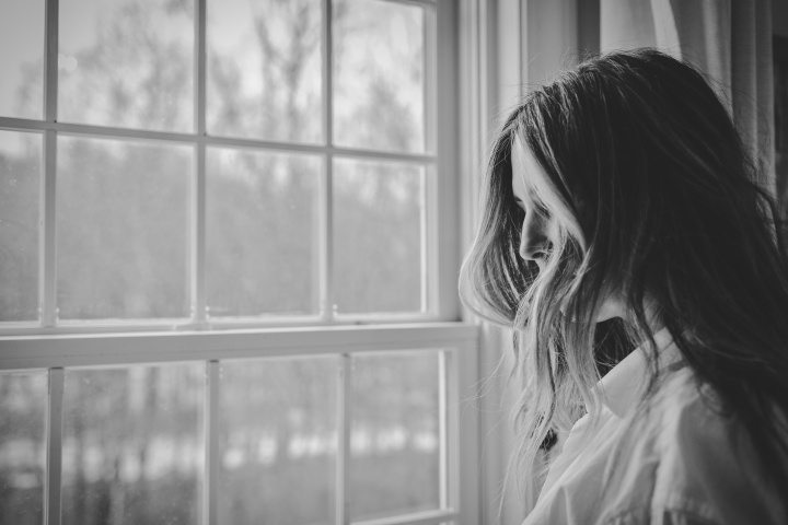 A young woman looking outside a window.
