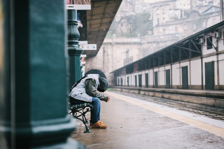 A man sitting a train terminal with his head down.