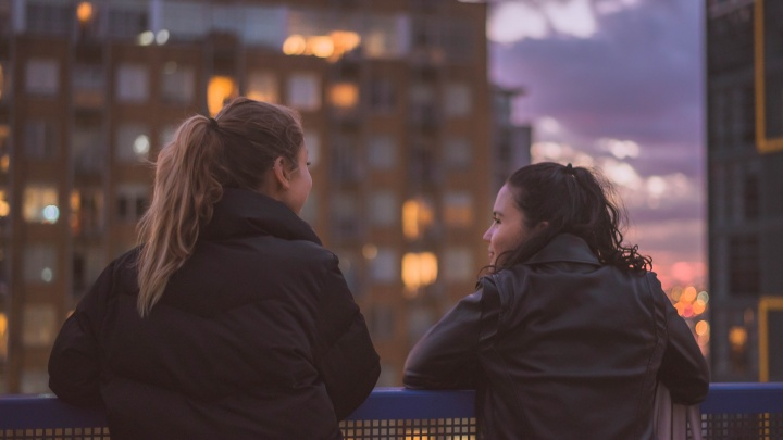 Two young women talking to each other.