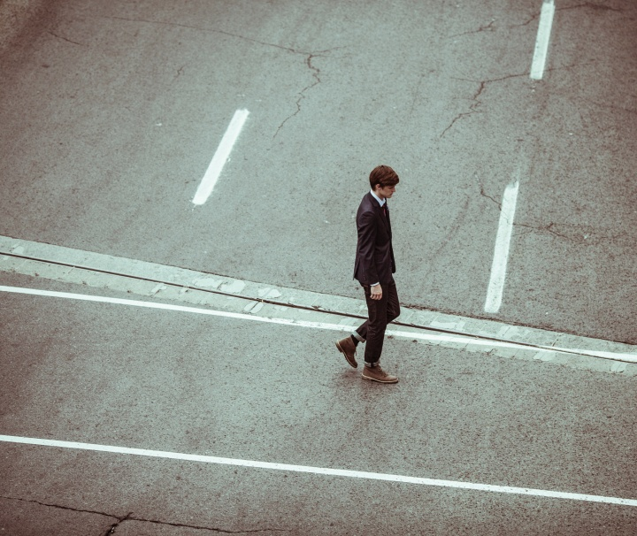 A young man in a suit walking across a road.
