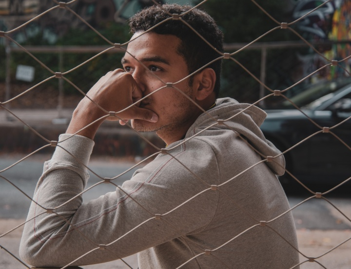 A young man sitting next to chain fence with his head on his hand.