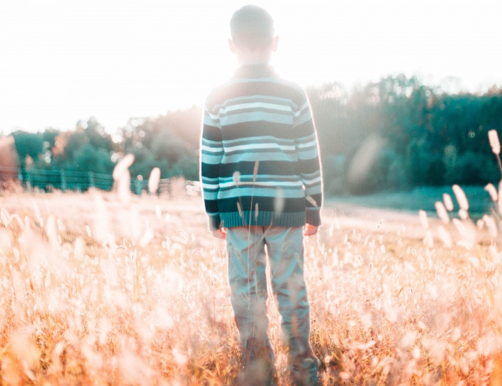 A young boy standing in a field.