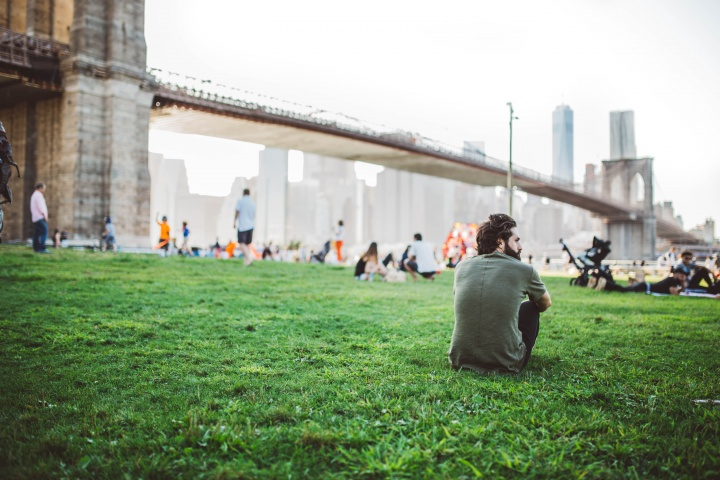 People sitting at a park by a large bridge.