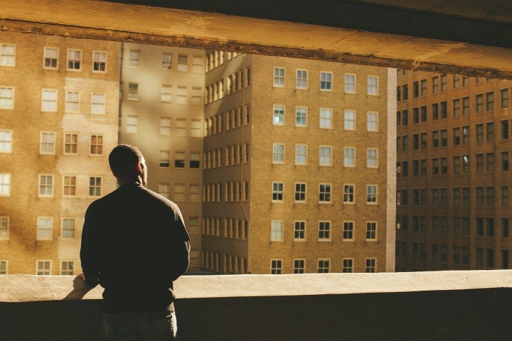 A person looking out over a wall at buildings in a city.