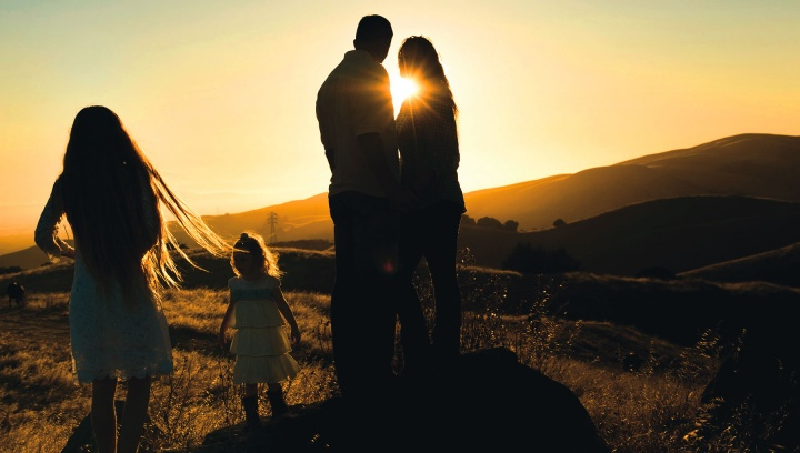 A family in a field at sunset.