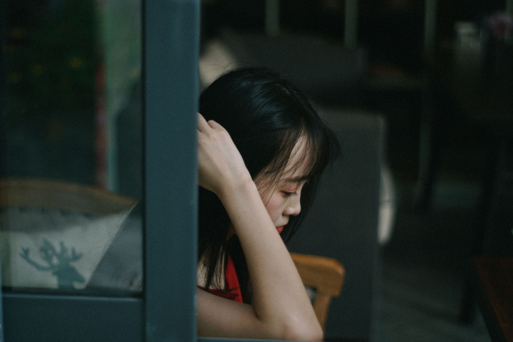 A woman looking depressed sitting by a window.