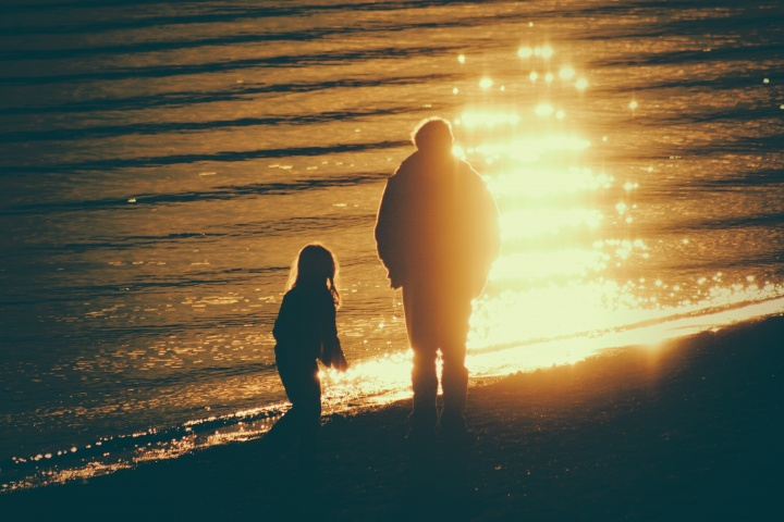 A dad and his children walking on the beach as the sun is setting.
